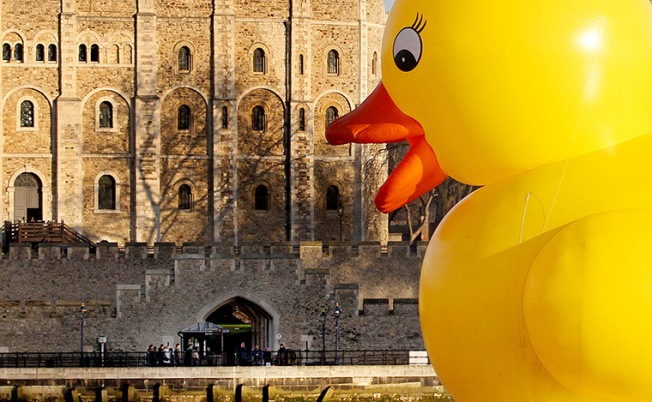 A giant 50 foot rubber duck floats past the Tower of London